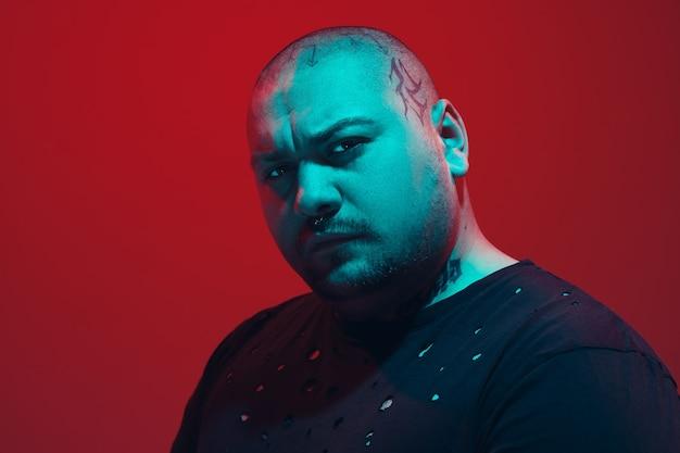 Porträt eines mannes mit buntem neonlicht auf roter wand. männliches model mit ruhiger und ernster stimmung. gesichtsausdruck, millennials lifestyle und aussehen. zukunft, technologien.