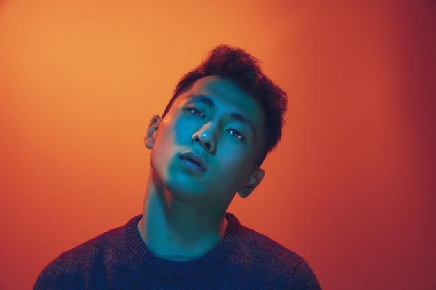 Porträt eines mannes mit buntem neonlicht auf steigungsstudiohintergrund. männliches model mit ruhiger und ernster stimmung. gesichtsausdruck, cyberpunk, millennials lifestyle und aussehen. zukunft, technologien.