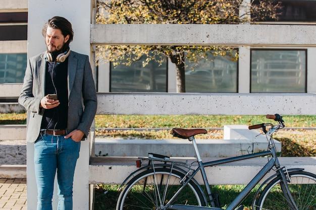 Porträt eines mannes mit dem handy in der hand, der nahe dem fahrrad steht