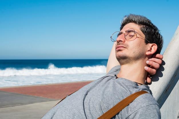 Porträt eines mannes mit den stillstehenden gläsern, die am strand sitzen