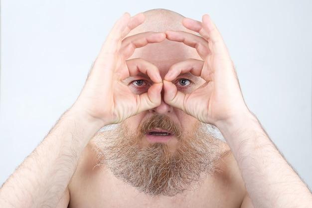 Porträt eines mannes mit einem bart, der durch seine finger schaut