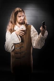Porträt eines mannes mit einem bart und langen haaren, die ein mittelalterliches piratenkostüm auf einem schwarzen raum tragen, ein pirat, der ein mobiltelefon hält
