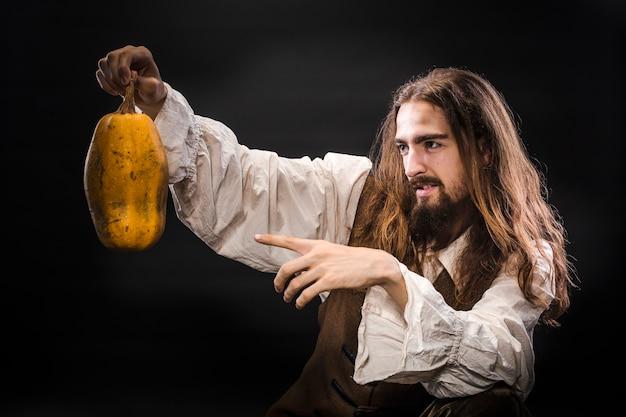 Porträt eines mannes mit einem bart und langen haaren, die ein mittelalterliches piratenkostüm auf einem schwarzen raum tragen, ein pirat, der einen reifen kürbis hält