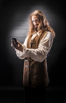 Porträt eines mannes mit einem bart und langen haaren, die ein mittelalterliches piratenkostüm auf einer schwarzen wand tragen, ein pirat, der ein mobiltelefon hält