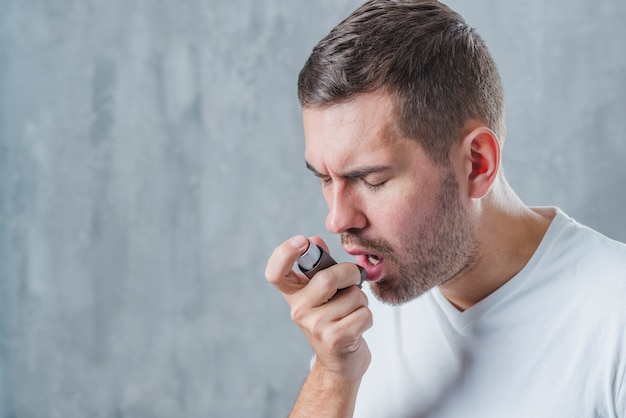 Porträt eines mannes mit geschlossenen augen mit asthma-inhalator