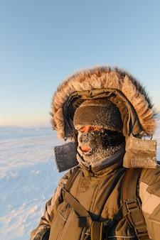 Porträt eines mannes mit geschlossener gesichtsmaske, dessen gesicht mit frost bedeckt ist.