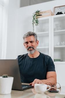 Porträt eines mannes mit grauen haaren, mitte 50, der von zu hause aus arbeitet