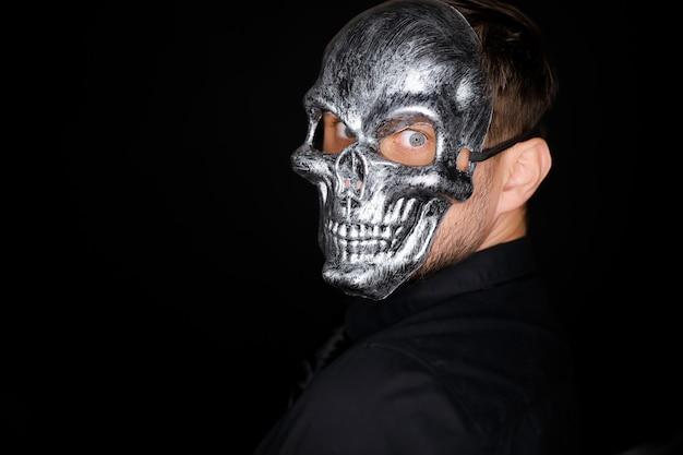 Porträt eines mannes mit skelettmaske wird zur kamera