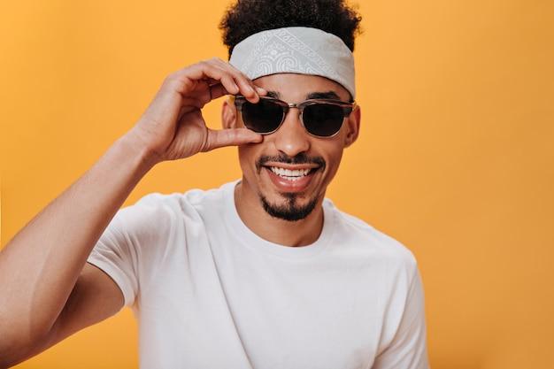 Porträt eines mannes mit sonnenbrille, der an einer orangefarbenen wand posiert