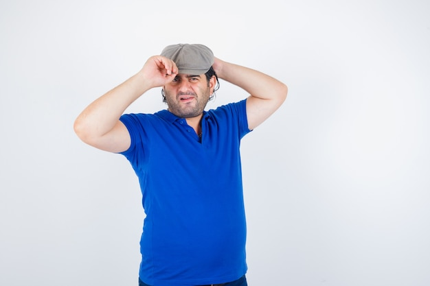 Porträt eines mannes mittleren alters, der seine mütze im polo-t-shirt, im efeuhut und in der unentschlossenen vorderansicht einstellt