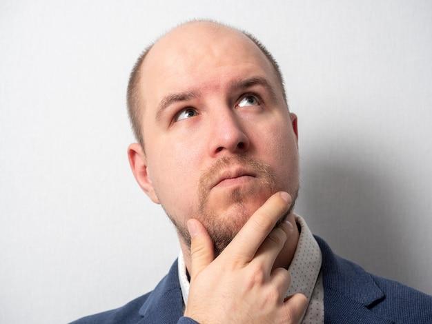 Porträt eines mannes mittleren alters in jacke und hemd, der nachdenklich aufschaut. eine hand hält seinen bart. emotionen, nachdenklichkeit, geschäftsmann, gesichtsbehaarung, kleine haare auf dem kopf