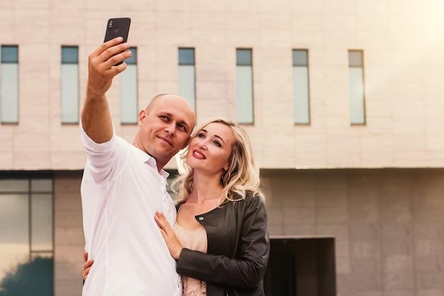 Porträt eines mannes und einer frau lächelnd, während selfie in der stadt nehmen