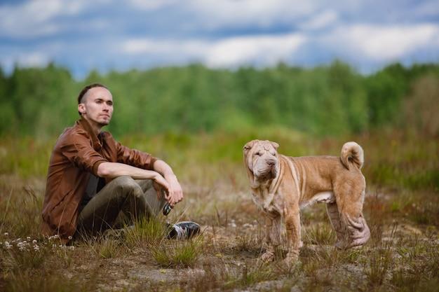 Porträt eines mannes und eines shar-pei-rassenhundes, die auf dem boden in einer wiese sitzen