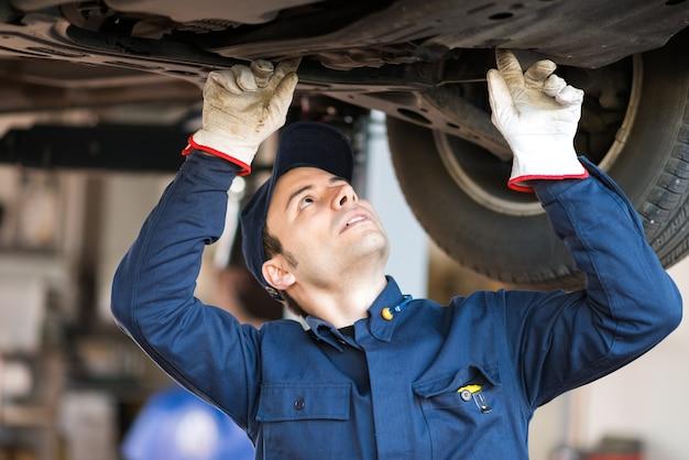 Porträt eines mechanikers, der die bedingung ein angehobenes auto überprüft
