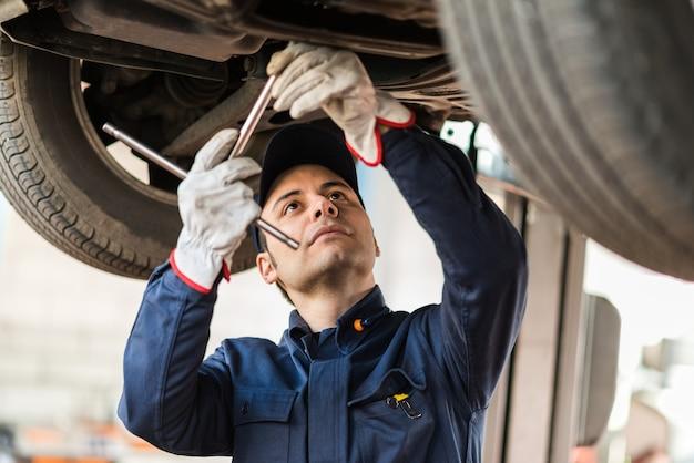 Porträt eines mechanikers, der ein angehobenes auto repariert
