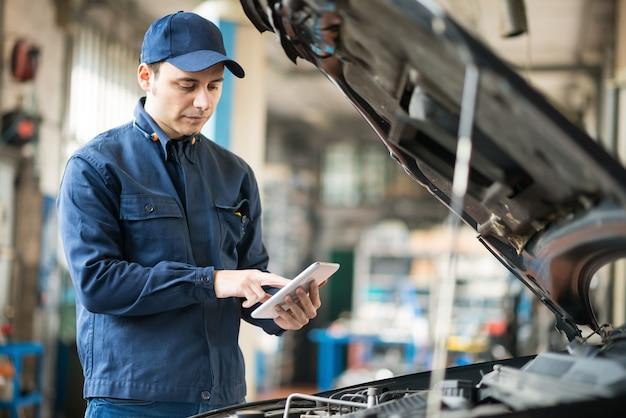 Porträt eines mechanikers, der eine tablette in seiner garage verwendet