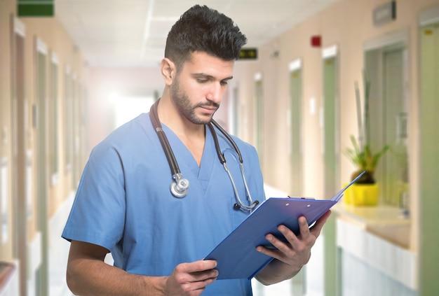 Porträt eines medizinischen arbeiters, der ein dokument auf einem klemmbrett liest