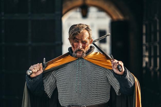 Porträt eines mittelalterlichen älteren kriegers in rüstung nach einem kampf mit blut im gesicht. der krieger hält zwei schwerter in seinen händen