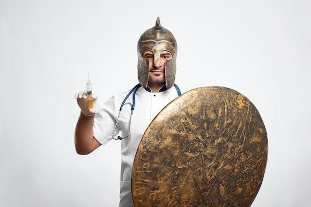 Porträt eines mittelalterlichen kriegerarztes in einem helm, der eine spritze hält