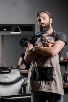 Porträt eines mittleren erwachsenen bärtigen männlichen friseurs mit den gefalteten armen