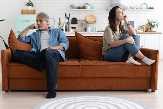 Porträt eines mittleren erwachsenen paares, das nach streit auf dem sofa sitzt.
