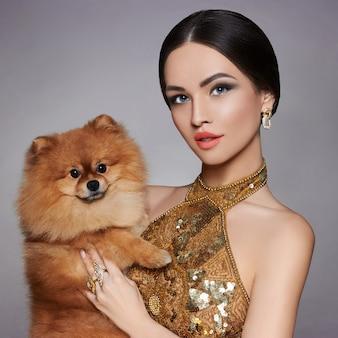 Porträt eines model mit einem kleinen hund in seinen händen