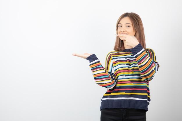 Porträt eines modells der jungen frau, das zur hand zeigt.