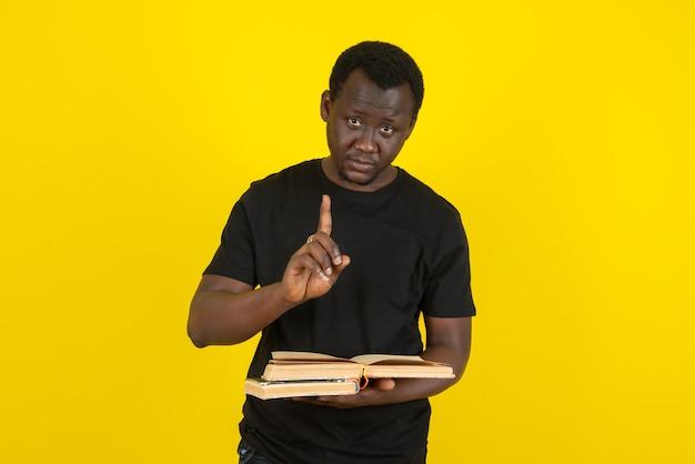 Porträt eines modells des jungen mannes, das bücher gegen gelbe wand hält