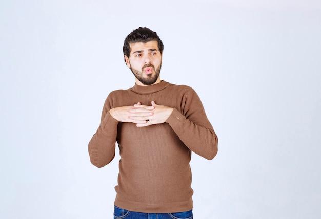 Porträt eines modells des jungen mannes, das händchen auf der brust steht und hält.