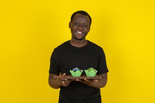 Porträt eines modells des jungen mannes, das köstliche kleine kuchen gegen gelbe wand hält