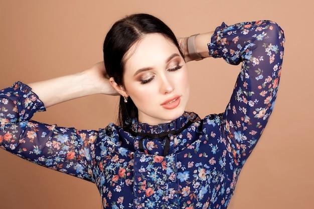 Porträt eines modells, eines schönen brünetten mädchens auf einem beigen hintergrund, in einem blauen kleid mit blauen augen. das konzept der weiblichen schönheit.
