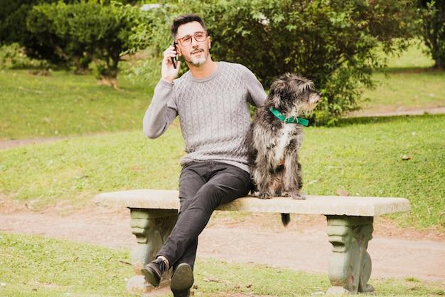 Porträt eines modernen mannes, der im park mit seinem hund spricht am handy sitzt