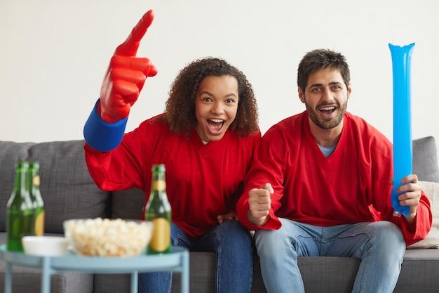 Porträt eines modernen paares gemischter rassen, das zu hause sportspiele im fernsehen sieht und emotional jubelt, während es rote teamuniformen trägt