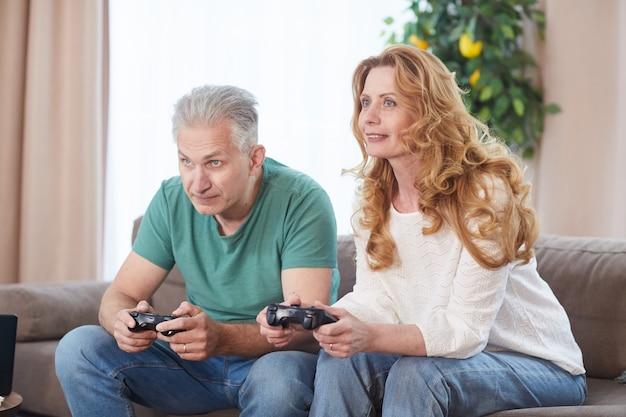 Porträt eines modernen reifen paares, das videospiele über konsole spielt und controller hält, während sie zeit zu hause genießen