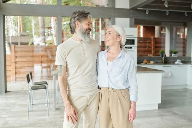 Porträt eines modernen seniorenpaares, das in einem großen haus lebt: sie umarmen sich gegen die küche