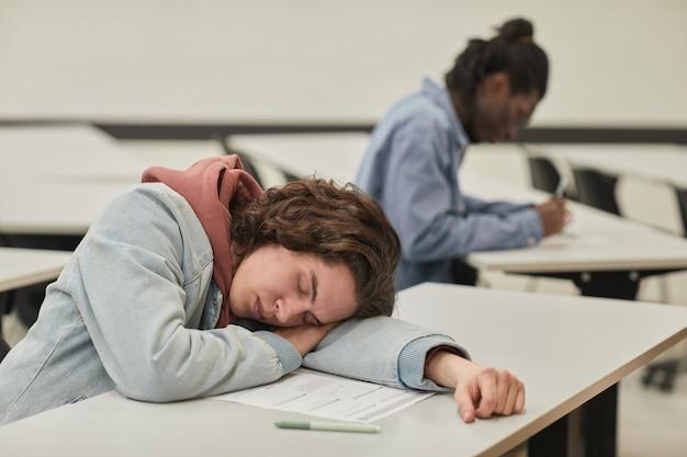 Porträt eines modernen teenagers, der auf dem schreibtisch im schulklassenzimmer schläft, kopierraum