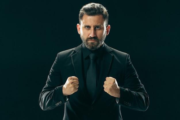 Porträt eines modischen jungen mannes mit stilvollem haarschnitt, der einen trendigen anzug trägt, der über einer schwarzen wand posiert