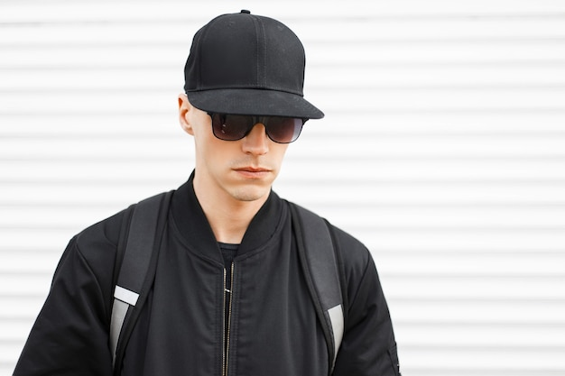 Porträt eines modischen mannes hipster in einer schwarzen mütze in stilvoller schwarzer sonnenbrille in einer trendigen jacke mit einem schwarzen rucksack auf seinen schultern an einer weißen wand. ernsthafter stilvoller amerikaner.