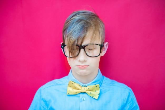Porträt eines modischen teenagers mit langen haaren und brille auf einem rosa