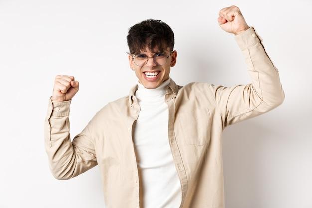 Porträt eines motivierten jungen mannes, der freude fühlt, hände hebt und den sieg feiert, triumphiert und ja sagt, auf weißer wand stehend.