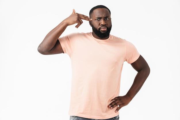Porträt eines müden afrikanischen mannes, der ein t-shirt trägt, das isoliert über einer weißen wand steht und eine waffe bei seiner tempelgeste zeigt