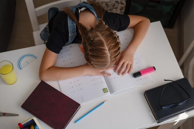 Porträt eines müden erschöpften kaukasischen rothaarigen, der auf ihren händen liegt, traurig aussieht, während er am schreibtisch sitzt und zu hause hausaufgaben macht. verzweifeln. online-bildung. quarantäne. zurück zum schulkonzept.