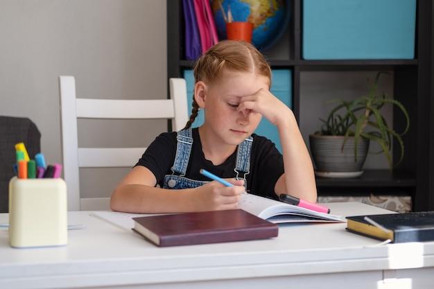 Porträt eines müden erschöpften kaukasischen rothaarigen, der traurig aussieht, während er am schreibtisch sitzt und zu hause hausaufgaben macht. verzweifeln. online-bildung. quarantäne. zurück zum schulkonzept.