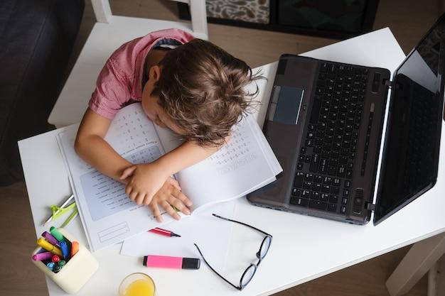 Porträt eines müden erschöpften kaukasischen schlafenden jungen, der auf seinen händen liegt, traurig aussieht, während er am schreibtisch sitzt und zu hause hausaufgaben macht. verzweiflung. online-bildung. quarantäne. zurück zum schulkonzept.