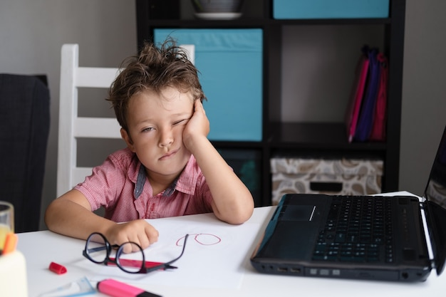 Porträt eines müden kaukasischen jungen, der seinen kopf hält, traurig aussieht, während er am schreibtisch sitzt und zu hause hausaufgaben macht. online-bildung. quarantäne. zurück zum schulkonzept.