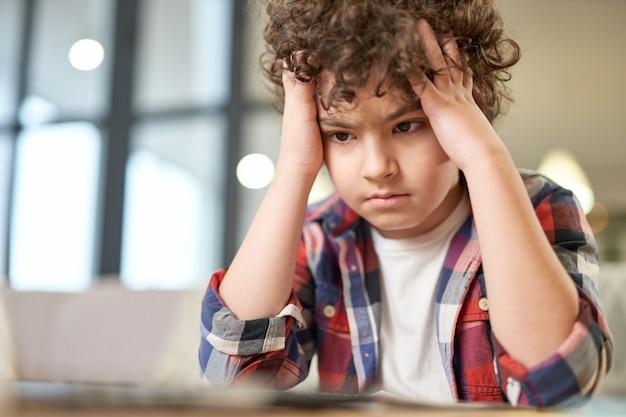Porträt eines müden lateinischen jungen, der seinen kopf hält, traurig aussieht, während er am schreibtisch sitzt und zu hause lernt. online-bildung, homeschooling-konzept