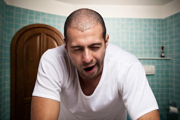 Porträt eines müden mannes, der im spiegel in seinem badezimmer schaut