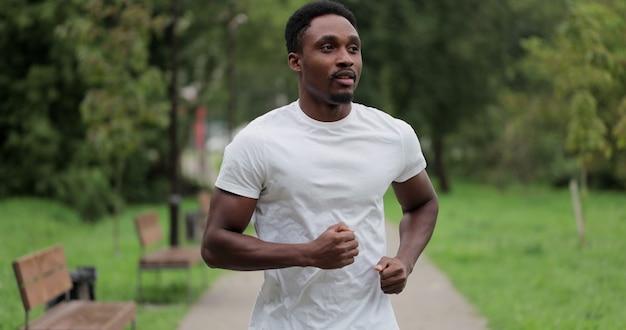 Porträt eines müden schwarzen läufers, der nach dem lauf im stadtpark atmet. der afroamerikanische sportler hat nach dem lauftraining im sommerpark eine pause. schließen sie herauf sportmann, der nach dem training im freien stillsteht.