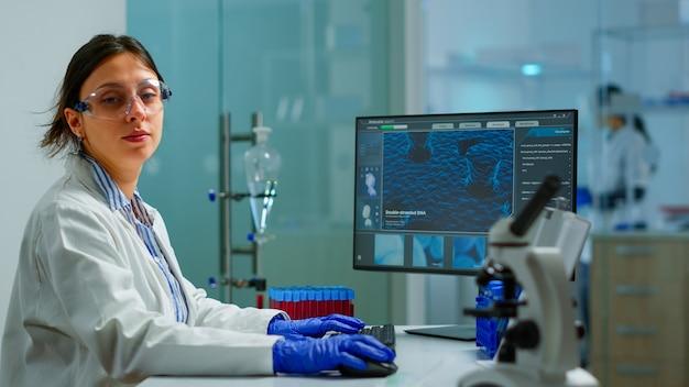 Porträt eines müden wissenschaftlers, der versucht, in die kamera zu lächeln, die in einem modern ausgestatteten labor sitzt und auf dem computer schreibt. chemiker untersucht die virusentwicklung mit hightech für wissenschaftliche forschung, impfstoff