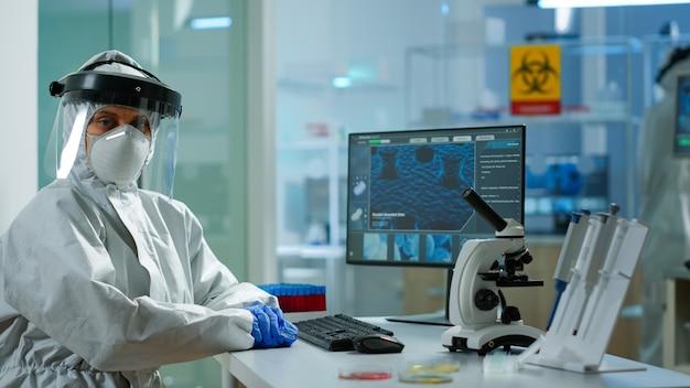 Porträt eines müden wissenschaftlers im overall mit blick auf die kamera, die in einem modern ausgestatteten labor sitzt. ärzteteam, das die virusentwicklung mit hightech- und chemiewerkzeugen für die impfstoffentwicklung untersucht.
